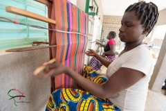 Woman weaving thread on a loom