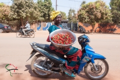 A woman selling strawberries on a motorcycle