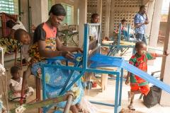 Woman weaving thread on a loom