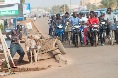 People on motorcycles next to a donkey