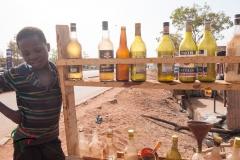 Boy standing next to bottles of motor oil