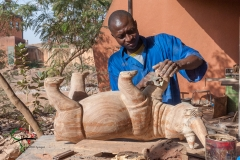A craftsman carving a wooden rhino
