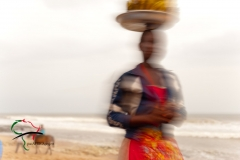 Woman carrying food on her head on the beach