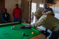 Men playing billards in a pool hall