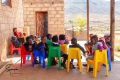 School children sitting down outside