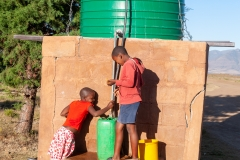 Children filling up containers at water tank