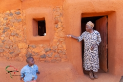 Elderly woman and child outside of their house