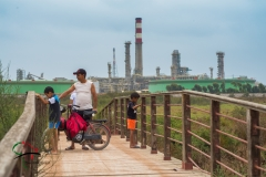 Father and sons standing on a bridge in front of a oil refinery