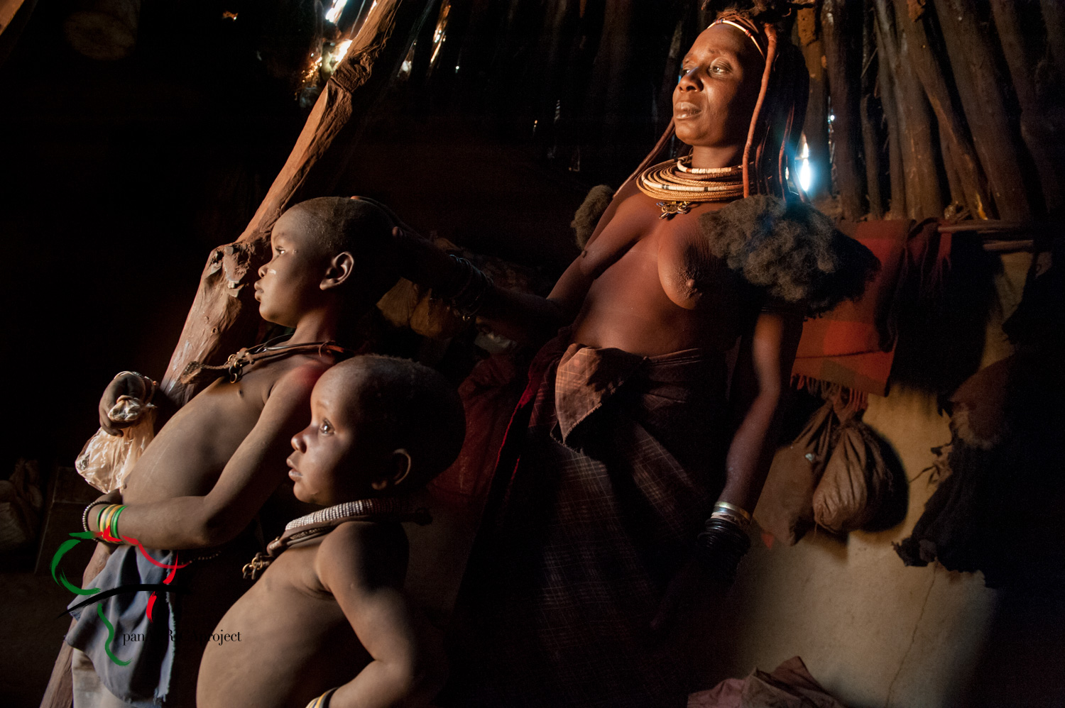Mother and son from the Himba Tribe inside their hut.