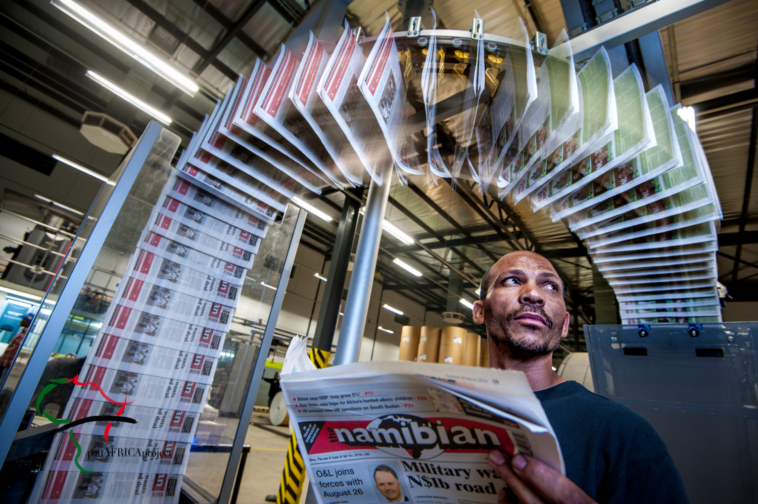 Newspapers running through a printing press while a worker reads one.