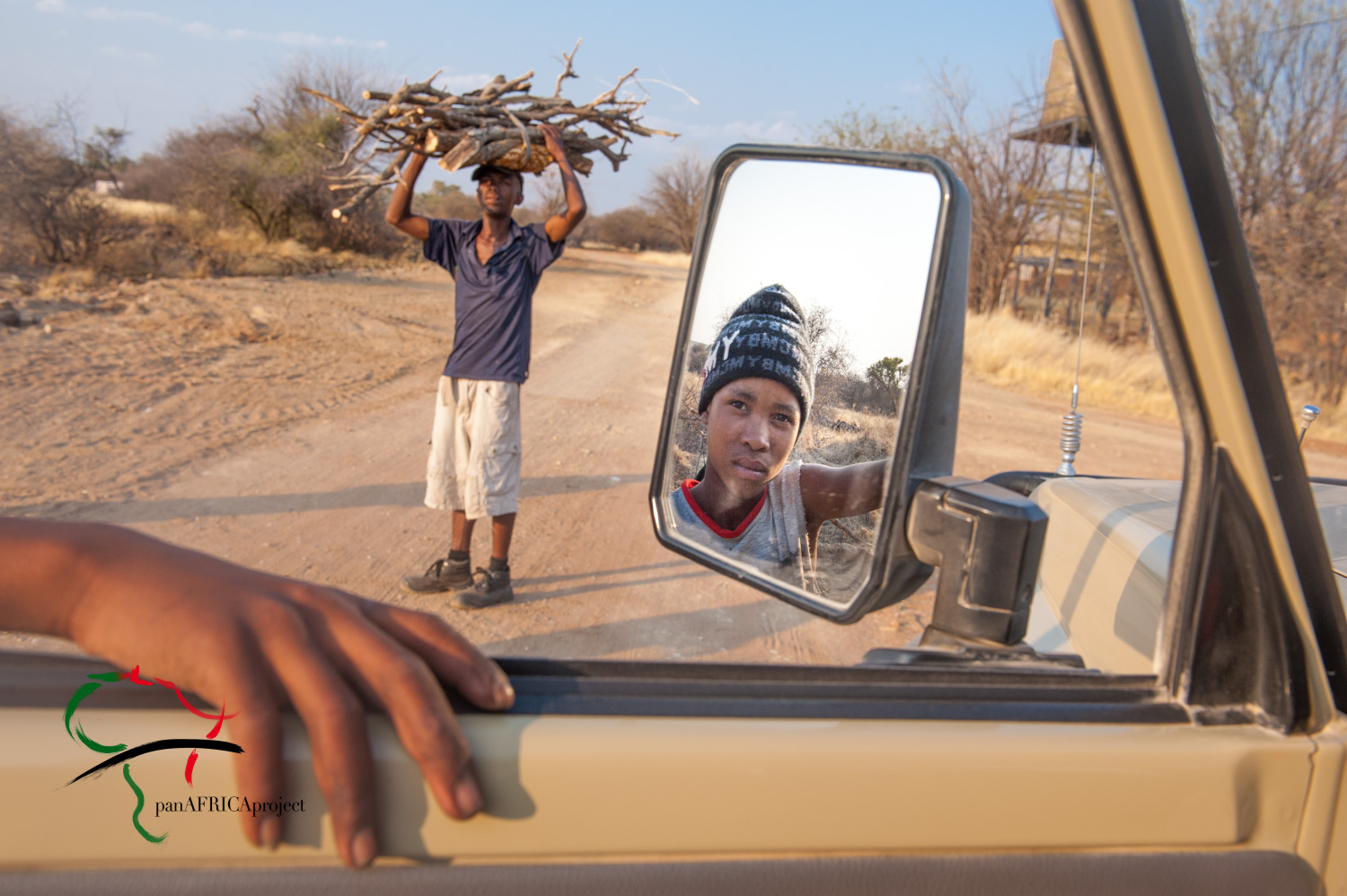 Man carrying firewood while child looks in mirror