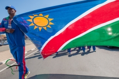 Male athlete leading a parade while holding Namibia flag.