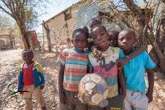 Portrait of children holding a soccer ball.