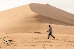 Man walking in front of sand dunes.