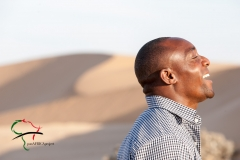 Profile of man in front of sand dunes.