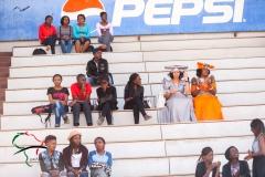 Spectators sitting on a grandstand.