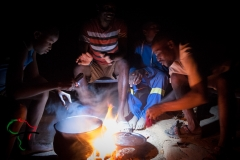 Men from the Herero Tribe cooking with an open flame.