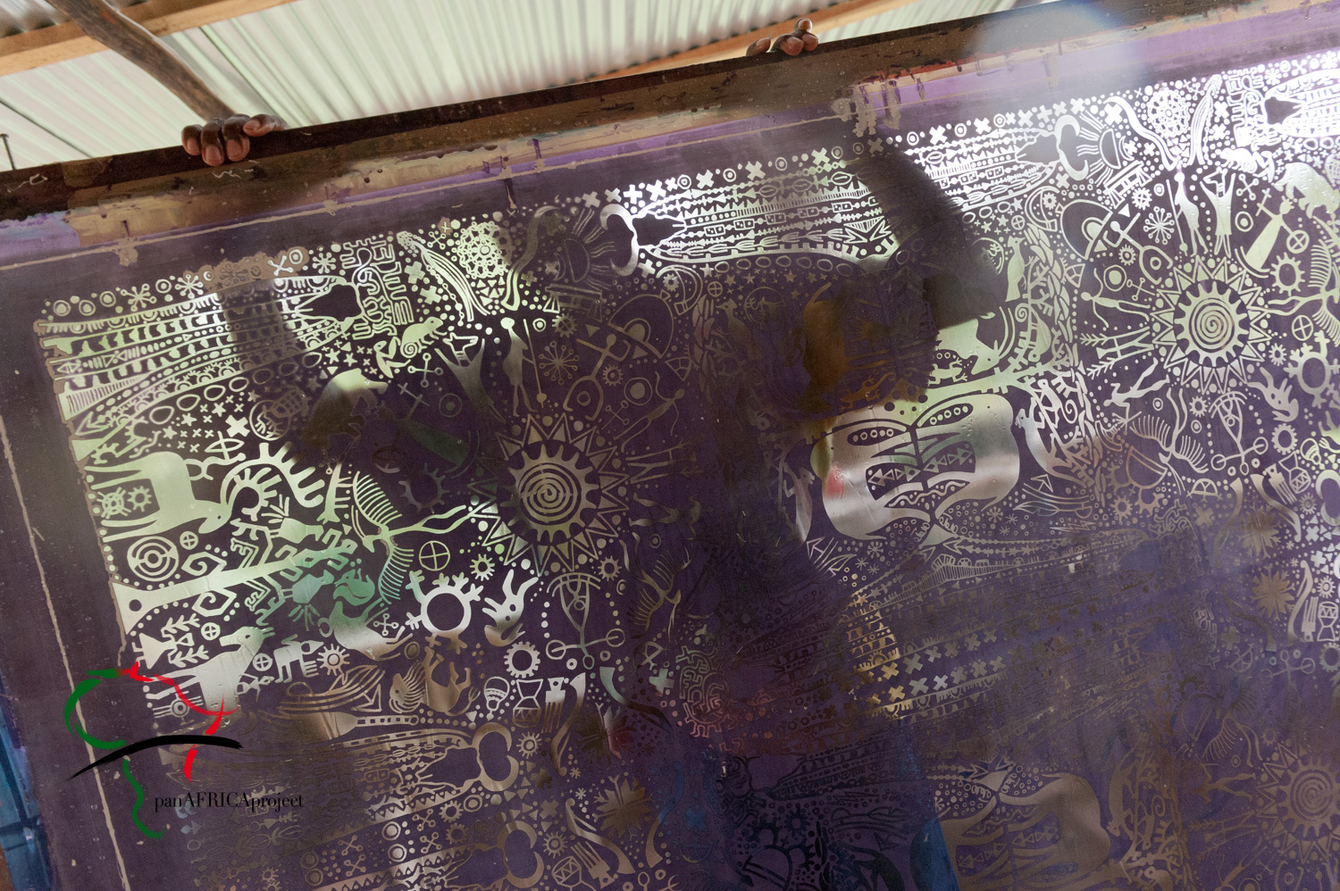 Artist standing behind a  silk screen