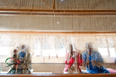 Women hand weaving a rug