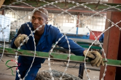 Factory worker looking through razor wire