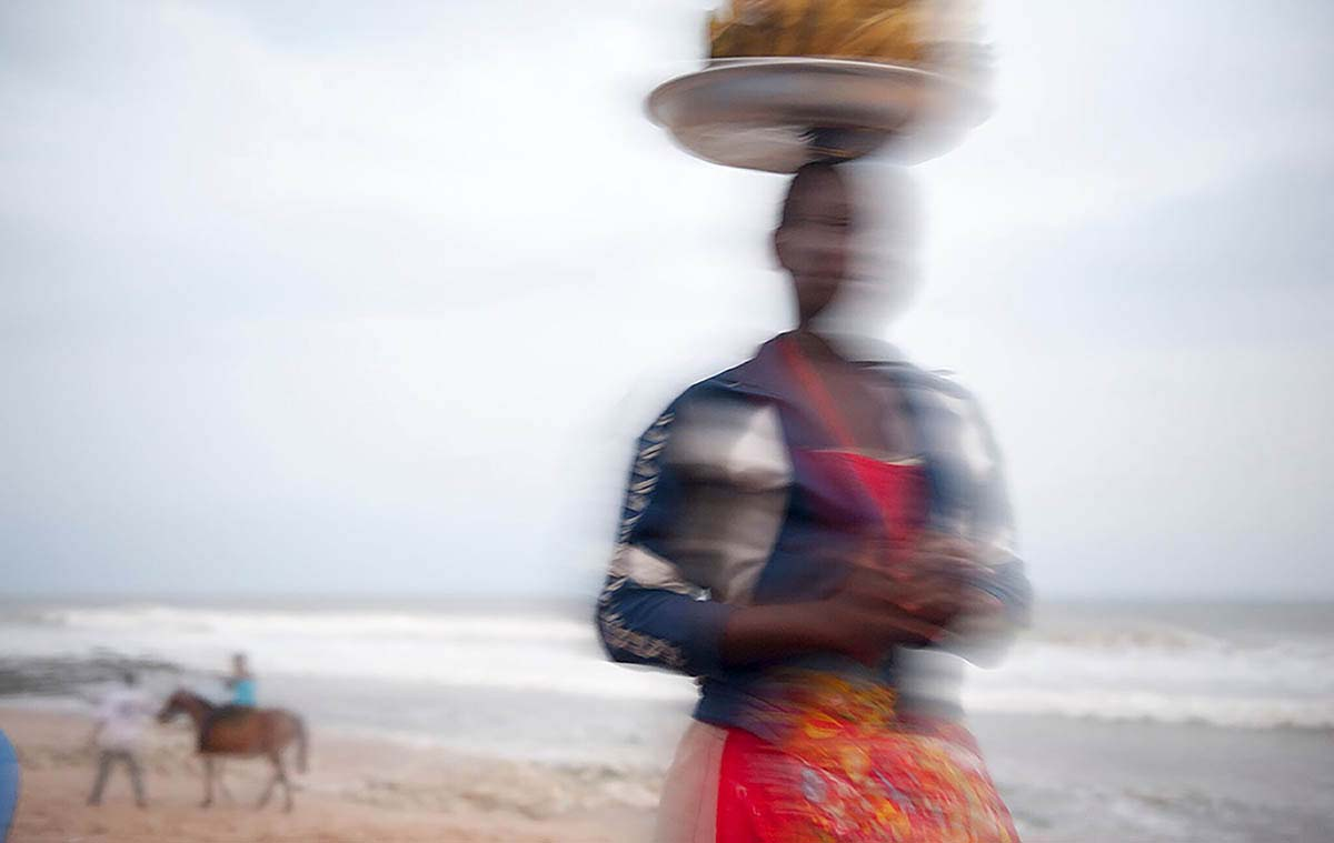 Woman carrying food on her head on the Tawala beach.