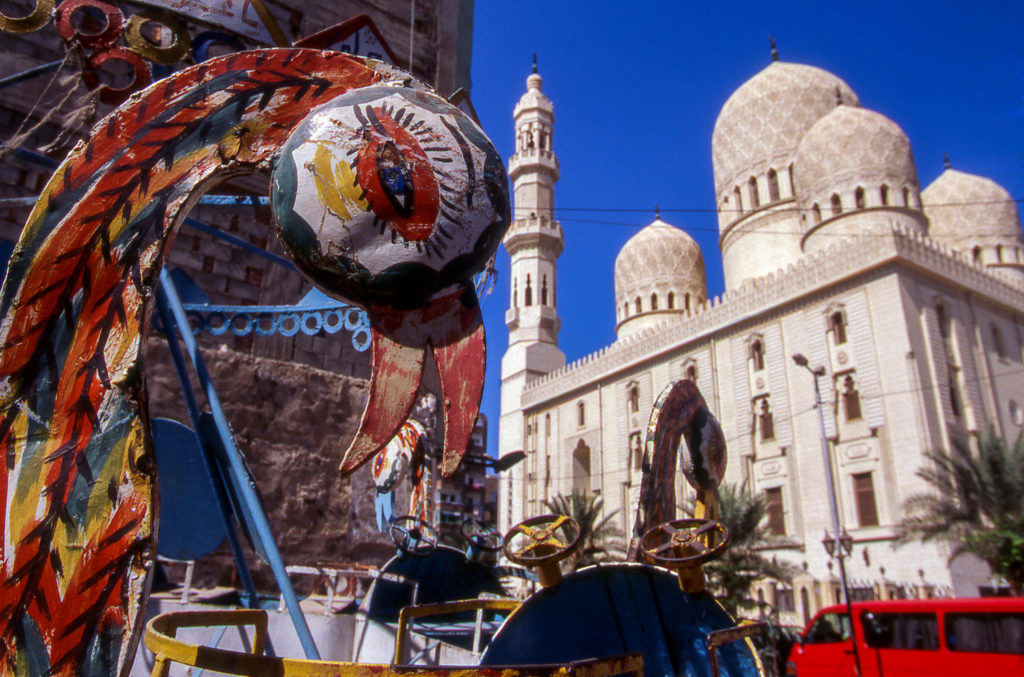 Carnival rides in front of the El-Mursi Abul Abbas Mosque