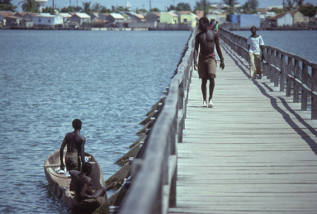 People walking on the bridge to Joal-Fadiouth