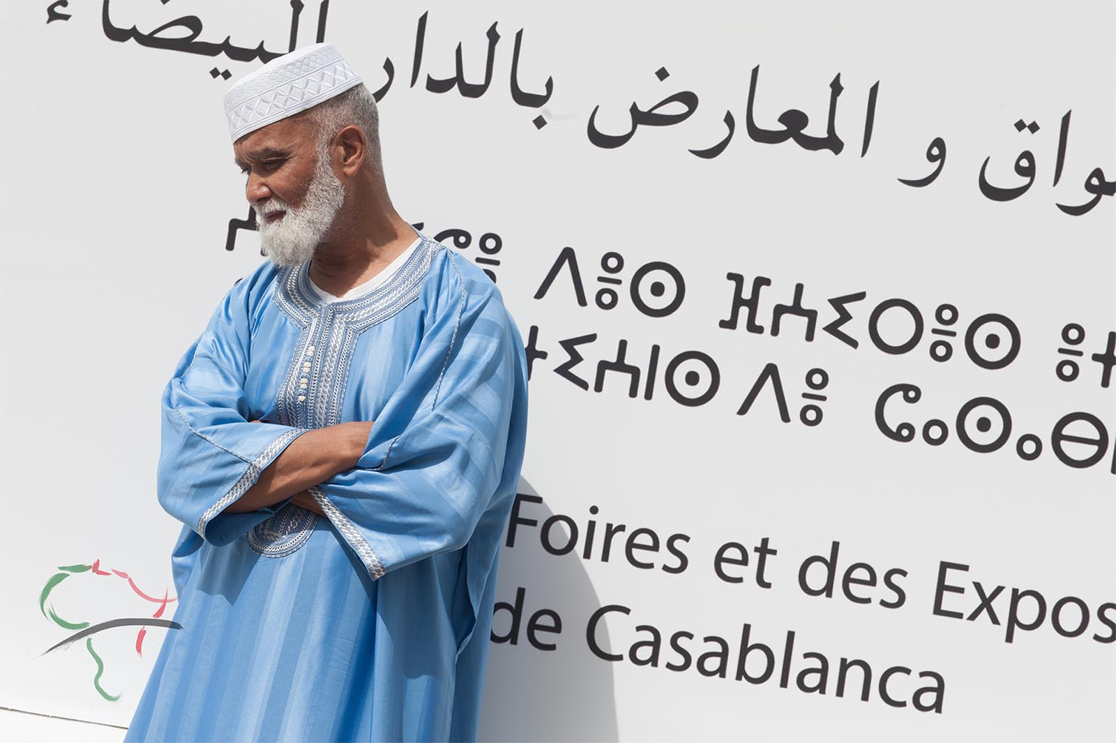 Portrait of man leaning on a wall with Arabic at Hassan II Mosque
