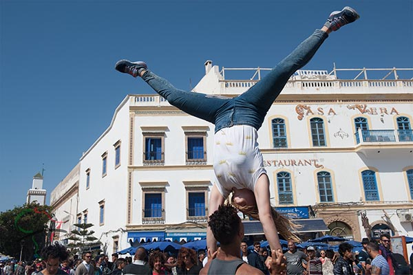 Buskers performing acrobatics for spectators at the Gnaoua World Music Festival